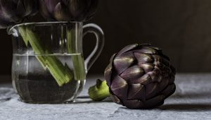 Photo of artichokes in a clear glass jar in water on a table cloth