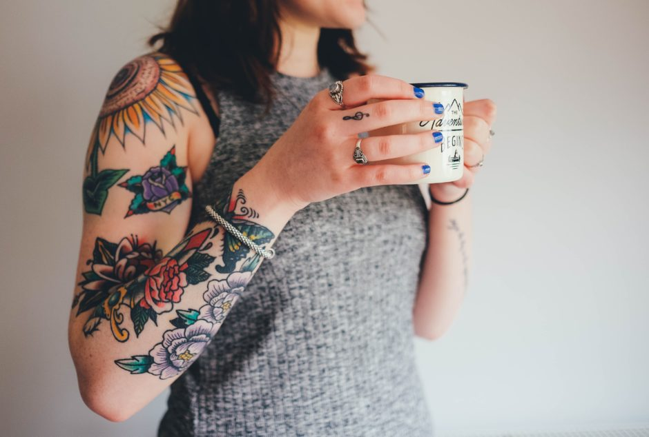 Women entrepreneur photo holding a morning coffee with tattoos by Annie Spratt