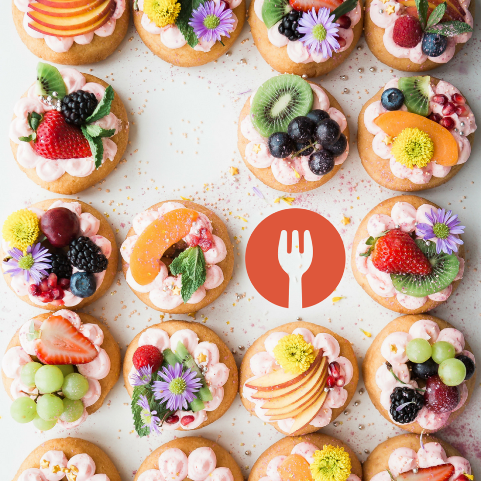 Many desserts arranged in neat rows with colorful toppings