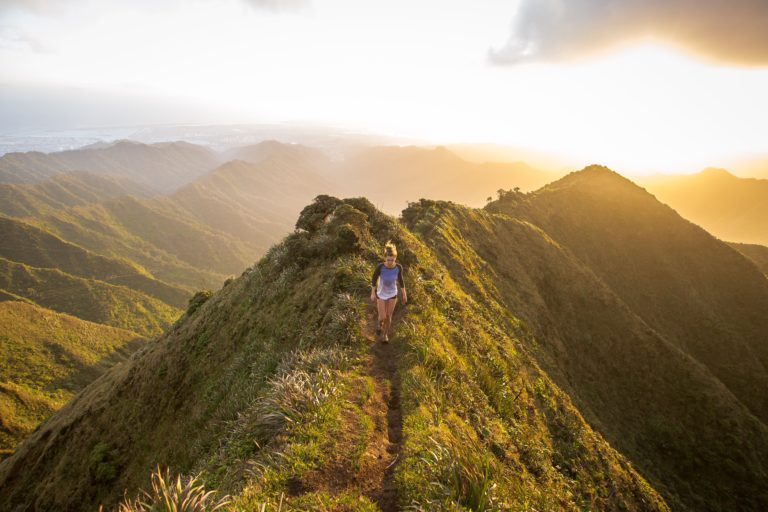 Beautiful Haiku Stairs in Hawaii, United States: mountain peaks in a tropical sunset with a woman trail running peacfully